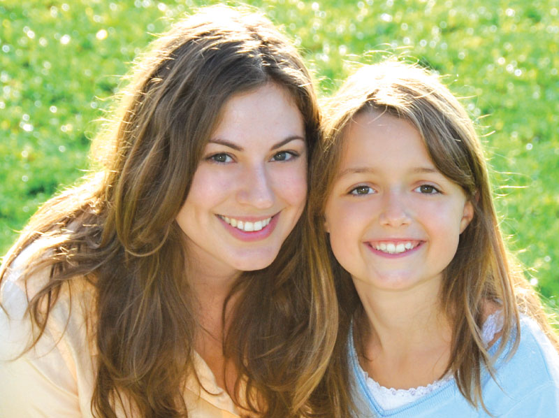 Mother and daughter smiling outside.