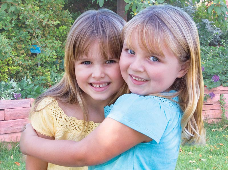 Two young girls hugging.